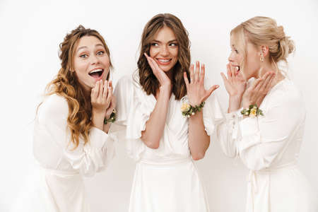 Photo of attractive happy bride showing her wedding ring at excited bridesmaids isolated over white wall