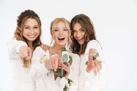 Photo of delighted young bride with her bridesmaids pointing fingers at camera isolated over white wall Standard-Bild