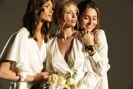Photo of young beautiful bride with her bridesmaids in white dresses posing with flowers on camera isolated over grey wall