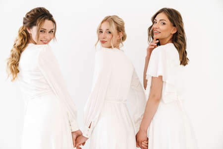 Photo from back of joyful charming three women holding hands together isolated over white wall