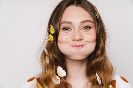 Photo of beautiful cheerful woman with fake butterflies blowing her cheeks isolated over white wall