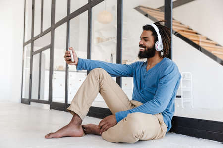 Cheerful young african man wearing wireless headphones making a videocall while sitting at home Banque d'images