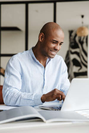 Photo of smiling african american man working with laptop while sitting at table in living room