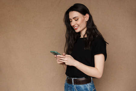 Photo of beautiful young brunette woman smiling and holding cellphone isolated over beige background