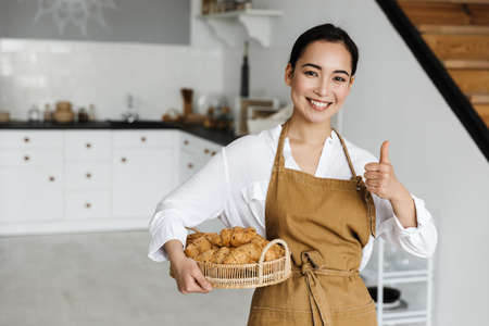 Smiling attractive young asian woman wearing apron standing at the kitchen at home, holding basket with fresh croissants