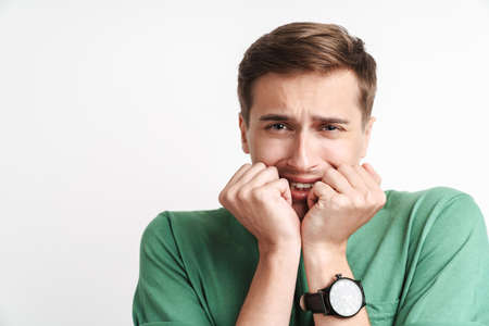 Image of displeased caucasian man in basic t-shirt being scared and shocked isolated over white background