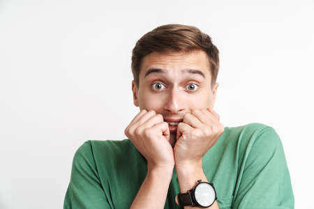 Image of stressed caucasian man in basic t-shirt being scared and shocked isolated over white background