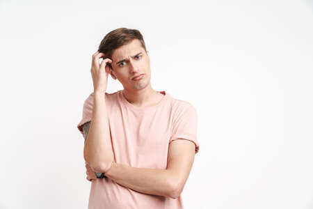 Image of brooding caucasian man in basic t-shirt thinking and scratching his head isolated over white background