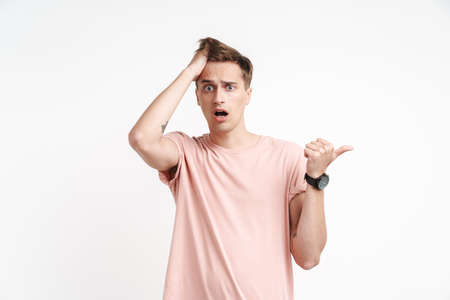 Image of shocked caucasian man in basic t-shirt screaming and pointing finger aside isolated over white background
