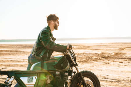 Handsome young man wearing leather jacket walking with a motorbike at the sunny beach