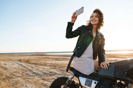 Beautiful young girl wearing leather jacket sitting on a motorbike at the sunny beach, taking a selfie