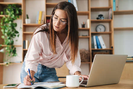 Image of concentrated adult businesswoman writing down notes while working with laptop at office