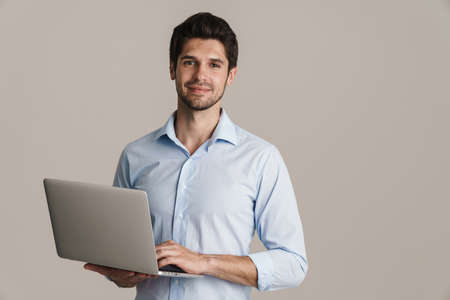 Image of smiling businesslike brunette man working with laptop isolated by beige background