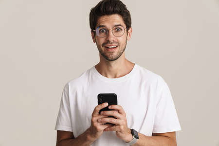 Image of surprised young man in eyeglasses using mobile phone isolated by white background
