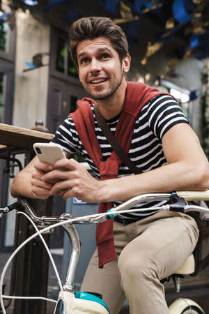 Image of cheerful handsome man smiling and using cellphone on bicycle at city street