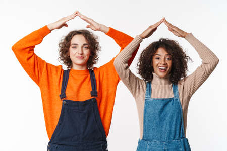 Portrait of funny multinational women in overalls making roof above their heads with arms isolated over white background Фото со стока