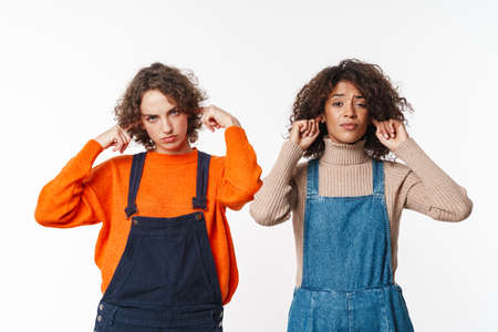 Portrait of serious multinational women in overalls plugging their ears and looking at camera isolated over white background
