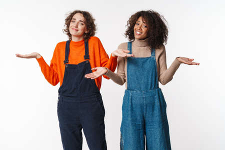 Portrait of cute multinational women in overalls looking at camera and throwing up hands isolated over white background