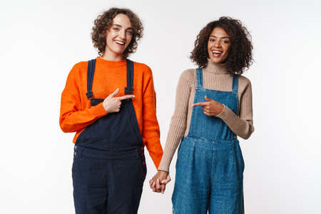Portrait of joyful women in overalls pointing fingers at each other and holding hands together isolated over white background