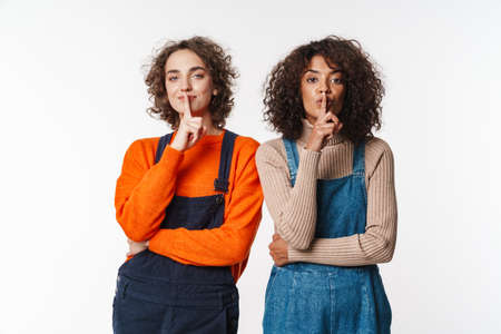 Portrait of curly multinational women in overalls gesturing silence sign at camera isolated over white background