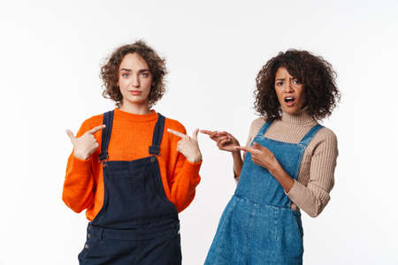 Portrait of two confused women in overalls looking at camera and pointing fingers isolated over white background