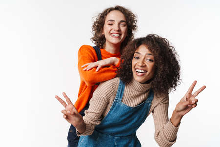 Portrait of joyful multinational women in overalls making fun and gesturing peace sign isolated over white background