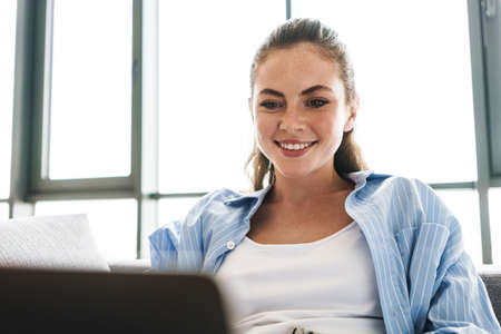 Image of a young happy smiling girl indoors at home using laptop computer Stock fotó