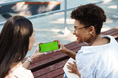 Top view of two happy young friends sharing blank screen mobile phone in the park