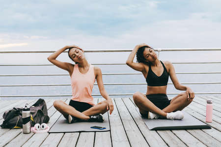 Image of focused multinational sportswomen stretching their necks while working out at promenade 版權商用圖片