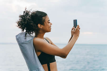Image of smiling african american sportswoman taking selfie on cellphone at promenade