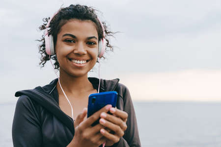 Image of smiling african american woman using cellphone and headphones while walking on promenade 版權商用圖片