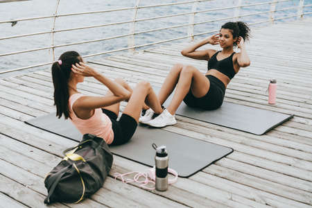 Image of focused multinational sportswomen working out on mats at promenade