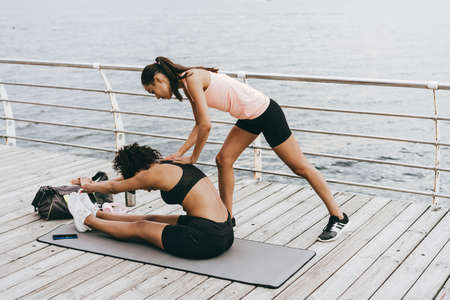 Image of focused african american sportswoman working out with coach at promenade 版權商用圖片