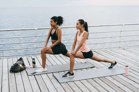 Image of focused multinational sportswomen doing exercise while working out on promenade
