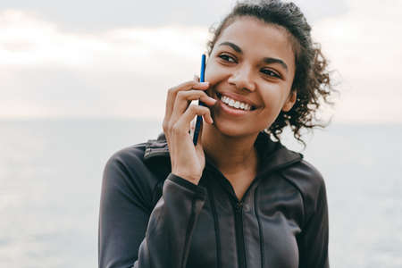 Image of smiling african american woman talking on cellphone while walking at promenade
