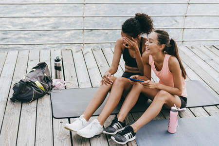 Image of laughing multinational sportswomen using cellphone while sitting on promenade
