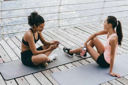 Image of happy multinational sportswomen using cellphone and drinking water on promenade 版權商用圖片