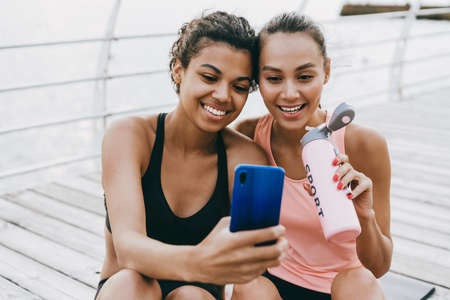 Image of cheerful multinational sportswomen taking selfie on cellphone while drinking water at promenade