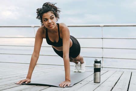 Image of focused african american sportswoman doing exercise while working out on mat at promenade 版權商用圖片