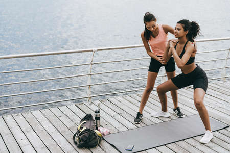 Image of pleased african american sportswoman working out with couch on promenade