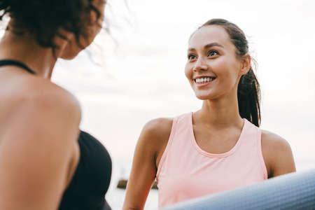 Image of joyful multinational sportswomen smiling and talking after workout at promenade
