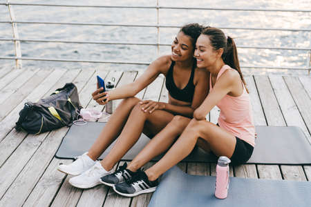 Image of cheerful multinational sportswomen taking selfie on cellphone while working out at promenade