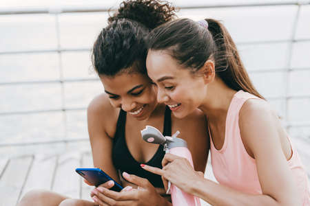 Image of smiling multinational sportswomen using and pointing finger at cellphone while sitting on promenade