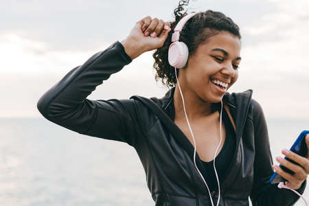 Image of smiling african american woman using cellphone and headphones while dancing on promenade