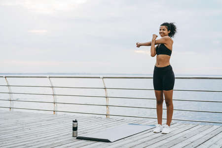 Image of smiling african american sportswoman doing exercise while working out on mat at promenade