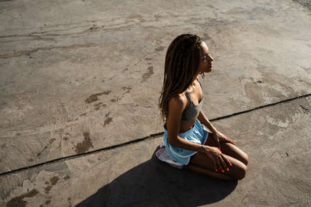 Image of calm african american girl in sportswear sitting on concrete promenade outdoors