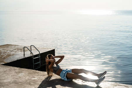 Young african sportswoman in headphones exercising outdoors at the beach pier