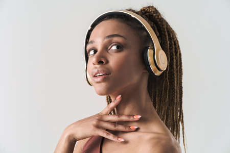 Close up portrait of beautiful african brunette woman with dreadlocks a listening music via wireless headphones isolated on white background