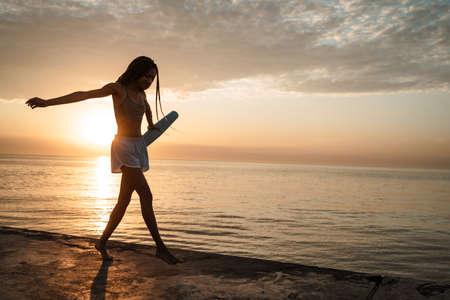 Image of happy african american girl in sportswear walking with mat on concrete promenade outdoors 版權商用圖片