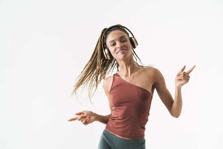 Image of a pretty positive african sports woman listening music with headphones while dancing isolated over white wall background